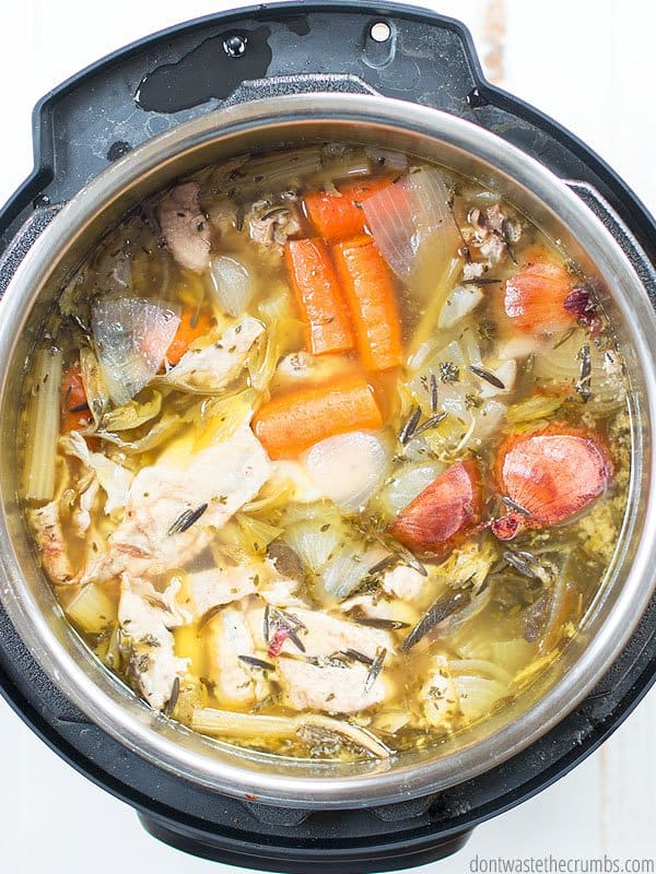Making homemade chicken stock is so easy in the Instant Pot. The image shows all the vegetable scraps, chicken scraps, and water about half done in an Instant Pot.