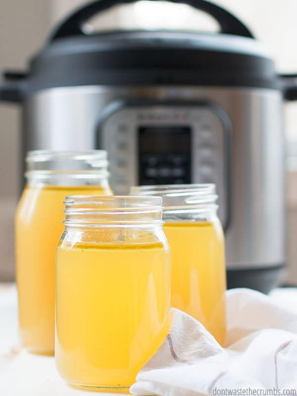 Learn how to make chicken stock in your Instant Pot pressure cooker with this simple tutorial. An Instant Pot is in the background of three full mason jars of chicken stock.
