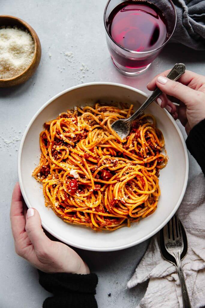 top shot of person holding fork and white bowl filled with Instant Pot spaghetti