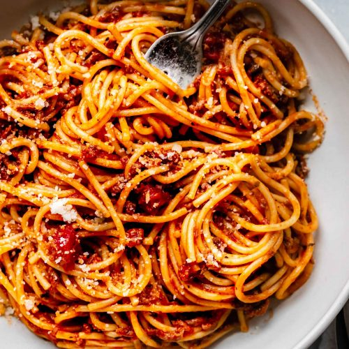 top shot of spaghetti noodles and tomato sauce in white bowl