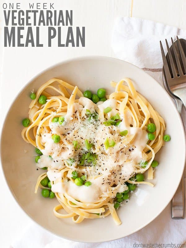 Overview of a white bowl filled with cooked pasta topped with cream sauce and peas. Text overlay One Week Vegetarian Meal Plan.